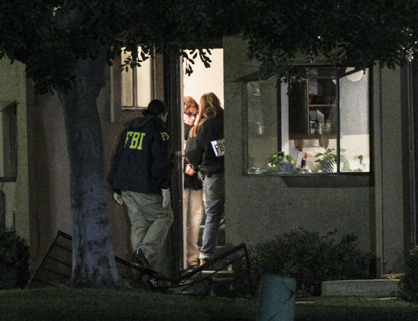 FBI agents search outside a home in connection with the shootings Wednesday in San Bernardino, Calif.