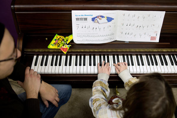 "Guitar, drums and piano instructor Loren Kranz (left) listens to Natalya Andrews, 8, play ""Up on the Housetop"" during Andrews' piano lesson. Kranz started teaching instrument lessons through Major Chords for Minors in September of 2014 and now gives lessons to 32 students Monday through Thursday."
