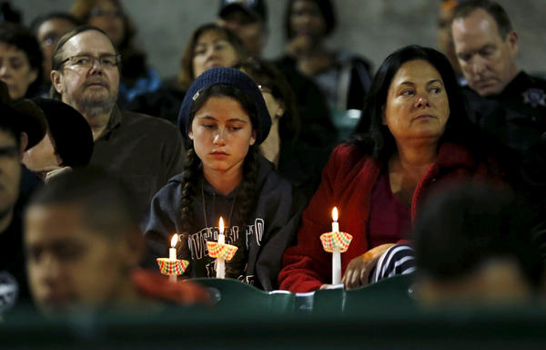 Attendees reflect on the tragedy of Wednesday's shooting attack during a candlelight vigil in San Bernardino on Thursday.