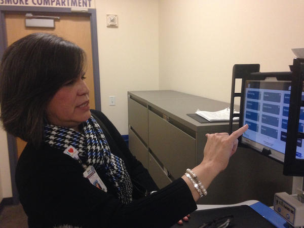 Rosalina Rivera shows off Seton family of hospitals' interpretation tablet. They are using the tablets to help refugees gain access to healthcare needs.