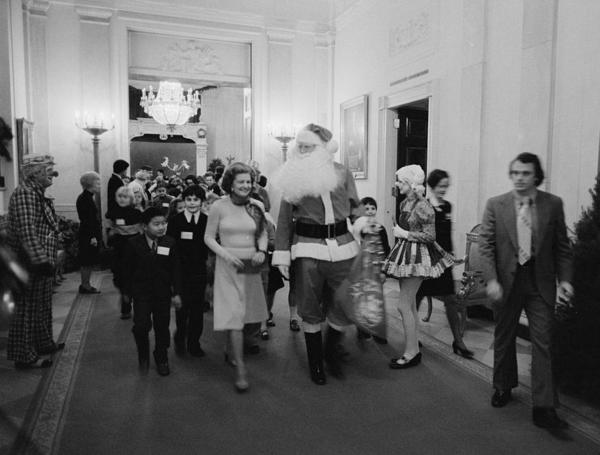 Holiday in the White House: First lady Betty Ford, Santa Claus and some clowns lead a procession of diplomatic corps children at a Christmas party in 1975.