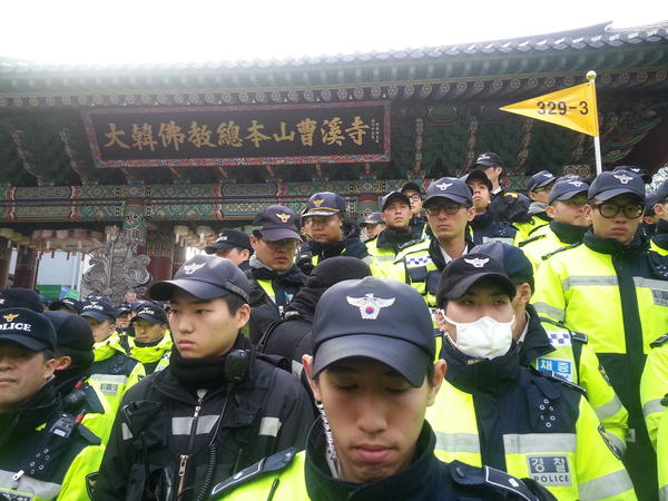Hundreds of police officers outside Jogyesa, Seoul's top Buddhist temple, as a deadline passed for a labor leader holed up inside to turn himself in.