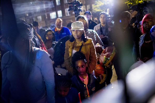 People attend a candlelight vigil in memory of 9-year-old Tyshawn Lee outside his father's home in Chicago last month.