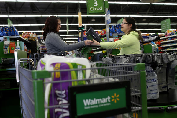 Wal-Mart employee Adriana Cajuso takes payment from customer Yoalmi Matias at a store in Miami. By mid-2016, Wal-Mart says, customers will have the option of paying via their smartphones.
