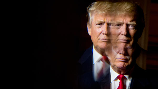 Donald Trump seen in a reflection while posing for a portrait following an interview with The Associated Press.