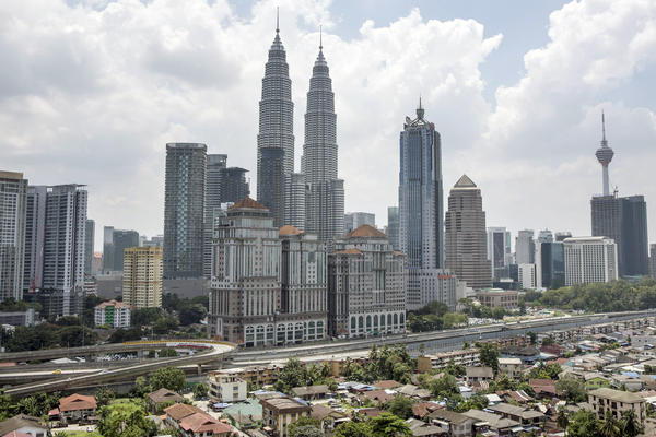 The Petronas Twin Towers rise over Kuala Lumpur, Malaysia's capital. The towers are a prime tourist destination, and buskers often perform there, now with government support.