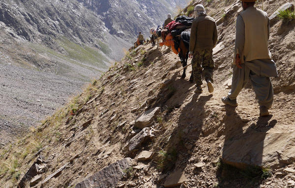 Porters and others navigate the steep descent from the mountains near the base camp, post-expedition.