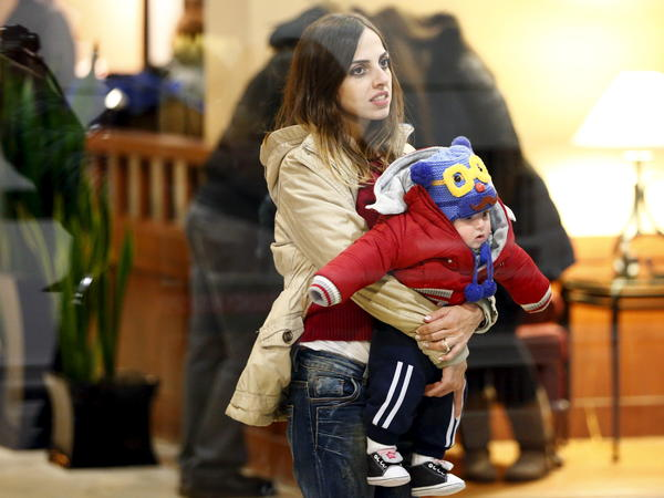 A Syrian refugee holds a child after arriving at a hotel in Mississauga, Ontario, on Dec. 11.