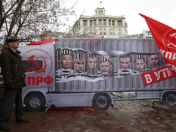 During a Dec. 5 protest against new highway fees in Moscow, a Russian Communist Party supporter stood in front of a banner with portraits of wealthy businessmen including billionaire Arkady Rotenberg, far left. Rotenberg's son, Igor Rotenberg, controls the business operating the new road fee system.