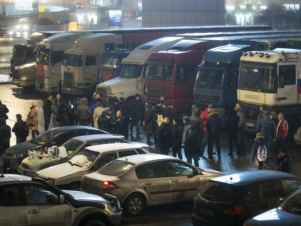 Truck drivers protesting new fees walk with supporters among parked trucks outside Moscow on Dec. 4.