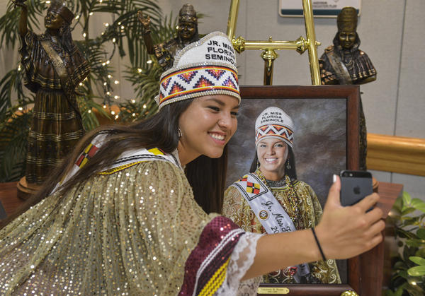 Outgoing Jr. Miss Florida Seminole Cheyenne Nunez snaps a selfie with her portrait at the Miss Florida Seminole pageant on July, 25, 2015 in Hollywood, Fla. Every Miss Florida Seminole from 2005 to the present has been memorialized in the bronze statues behind her.