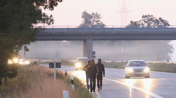 Three migrants from Afghanistan walk along the A3 highway shortly after they crossed into Germany on August 30, 2015, near Neuhaus am Inn, Germany. Police detained them shortly after and took them to a registration center for asylum seekers. Germany has welcomed many refugees — but now is discouraging Afghans who are seeking better economic prospects.