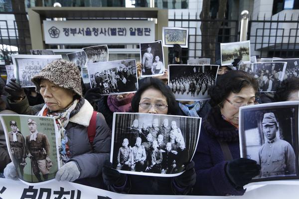 Relatives of Korean women forced into Japanese-run brothels during World War II demonstrate outside the foreign ministry in Seoul, South Korea, on Monday. The two countries announced a deal that included an apology from the Japanese prime minister and a fund to support the 46 surviving Korean women.