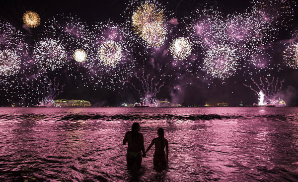 A couple watches fireworks exploding over Copacabana Beach in Rio de Janeiro on Jan. 1. Some 2 million people visit the beach on New Year's Eve. Lifeguards say they usually perform more rescues than any other time of the year.