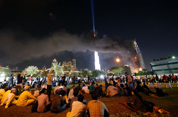 People watch the Address Downtown hotel burning on Thursday after a huge fire ripped through the luxury hotel in Dubai.