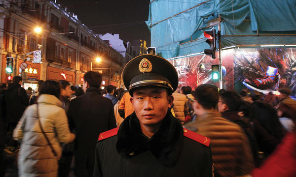 "A security personnel stands on patrol on New Year's Eve on the historic riverfront known as ""the Bund"" in Shanghai."