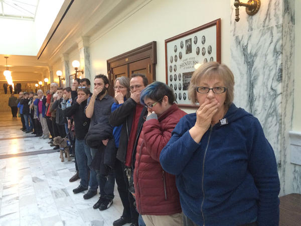'Add The Words' supporters stood in the hall after an Idaho House panel rejected the anti-discrimination bill. They held their hands to their mouths to represent their voices not being heard.