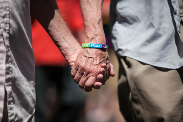 A couple holds hands at a gay pride rally in Portland June 14, 2015.