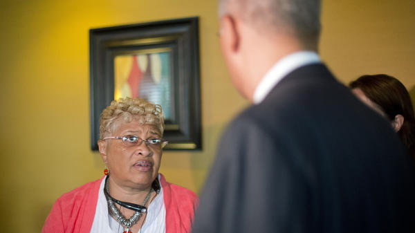 Attorney General Eric Holder (right) listens to Viola Murphy, mayor of Cool Valley, Mo., before his meeting with local community leaders in August 2014. Murphy is a vocal critic of new municipal regulations.