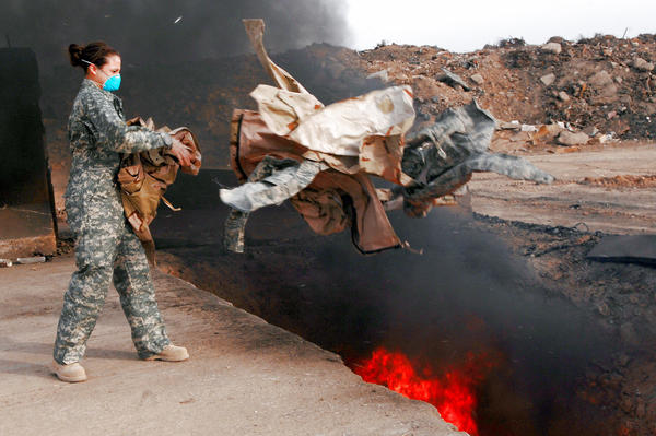 Senior Airman Frances Gavalis tosses unserviceable uniform items into a burn pit at Balad Air Base, Iraq in 2008. The military destroyed uniforms, equipment and other materials in huge burn pits in Iraq and Afghanistan. Some veterans say those pits are responsible for respiratory problems they are now experiencing.