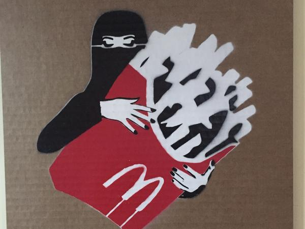 "A veiled woman with fries, from the ""LoudArt"" exhibit in Jeddah, Saudi Arabia. The piece is by Mohammed Labban."