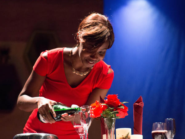 Ade, played by Nana Sam Elliott-Sackeyfio glows in new love at a private dinner, in the production of <em>Bananas and Groundnuts.</em>