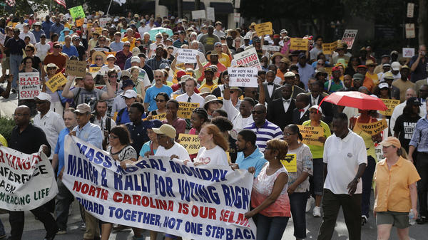 Demonstrators march through the streets of Winston-Salem, N.C., in July 2015, after the beginning of a federal voting rights trial challenging a 2013 state law. The most controversial part of that law — requiring voters to show photo identification at the polls — goes into effect this week, although its language was softened slightly last summer.