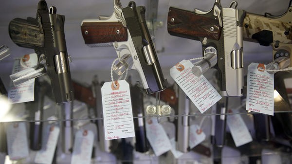 Handguns sit in a glass display case at Metro Shooting Supplies in Bridgeton, Mo.