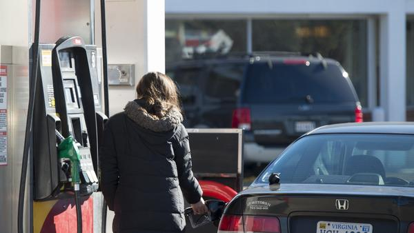 A woman fills her car with gas in Woodbridge, Va., on Tuesday. Supplies of crude oil and refined gasoline have driven prices at the pump down, and they're expected to go even lower.