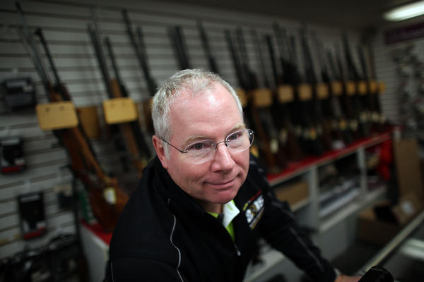 Karl Durkheimer, owner of Northwest Armory gun store in Portland, stands behind the counter Tuesday.