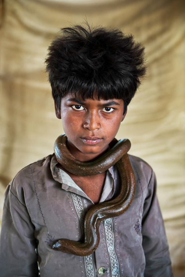 Vijay Nath, 12 exhibits his harmless sand boa. His family stays on the lookout for police: Snake handling has been outlawed since 1972. Gujarat, India, 2009.
