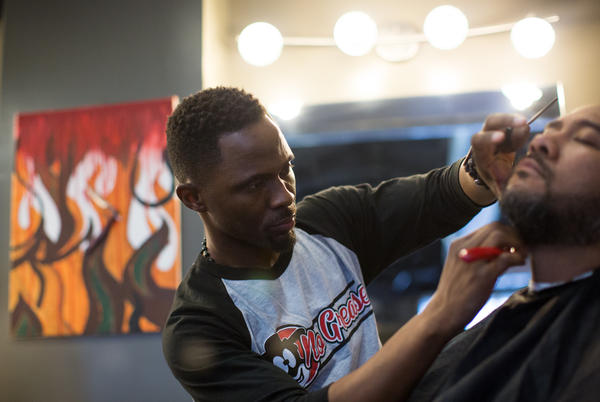 Damian Johnson, owner of No Grease Barber Shop in Charlotte, N.C., finishes up a haircut on Sam Chaney. Sam has been a client for over 10 years.