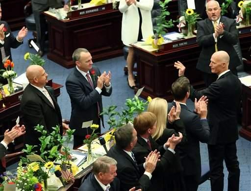 Gov. Rick Scott, right, waves as he is recognized by the Florida House at the start of the legislative session Tuesday in Tallahassee
