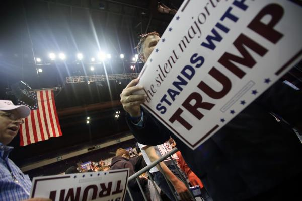 Supporters hand out placards during Republican presidential candidate Donald Trump's campaign rally in Pensacola, Fla.