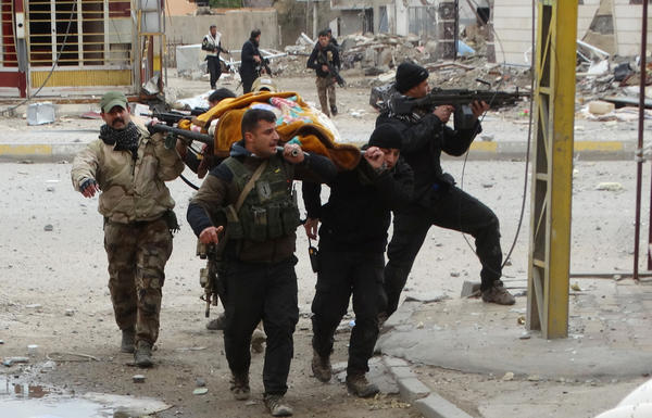 Iraqi security forces and allied Sunni tribal fighters evacuate an injured woman after she was shot by the Islamic State in Ramadi on Jan. 4. Iraqi forces have pushed ISIS out of much of Ramadi, but daily fighting is still taking place in the southeast part of the city, where ISIS is using civilians as human shields, according to the Iraqi military.