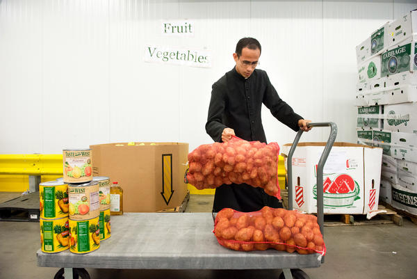Brother William Valle of the Institute of the Incarnate Word in Chillum, Md., loads potatoes onto his cart at the Capitol Area Food Bank, in Washington, D.C. A new government initiative seeks to engage faith-based groups on food waste — for instance, by using their existing relationships with food banks to redirect excess food to the hungry.