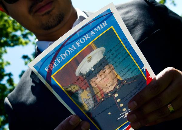 A man reads a flier with a photo of U.S. Marine veteran Amir Hekmati on May 19, 2014, during a vigil held in Lafayette Park across from the White House in Washington, D.C. The vigil was held on the 1,000th day of Amir's imprisonment in Iran. Hekmati was set to be released Saturday as part of a prisoner exchange.