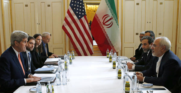 U.S. Secretary of State John Kerry (left) meets with Iranian Foreign Minister Mohammad Javad Zarif (right) in Vienna on Saturday. The International Atomic Energy Agency, or IAEA, has verified that Iran has met all conditions under the nuclear deal.