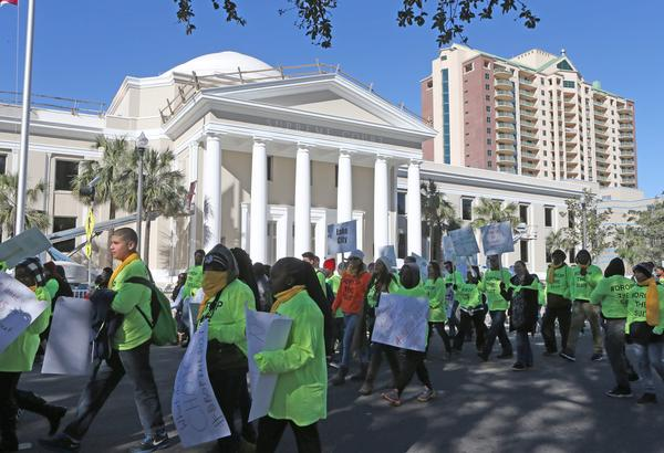 Demonstrators march by the Florida Supreme Court building just behind the Capitol as they rally in support of the school voucher program Tuesday
