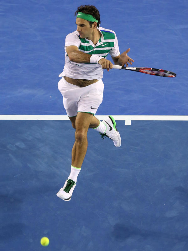 Roger Federer of Switzerland hits a forehand in his match against Grigor Dimitrov of Bulgaria on his way to winning his 300th Grand Slam match Friday at the Australian Open in Melbourne.