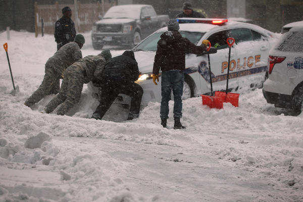 """National Guard members and other people help to push a police car that got stuck in the snow on Jan. 23 in Washington, D.C. Heavy snow continued to fall in the Mid-Atlantic region causing """"life-threatening blizzard conditions"""" and affecting millions of people."""