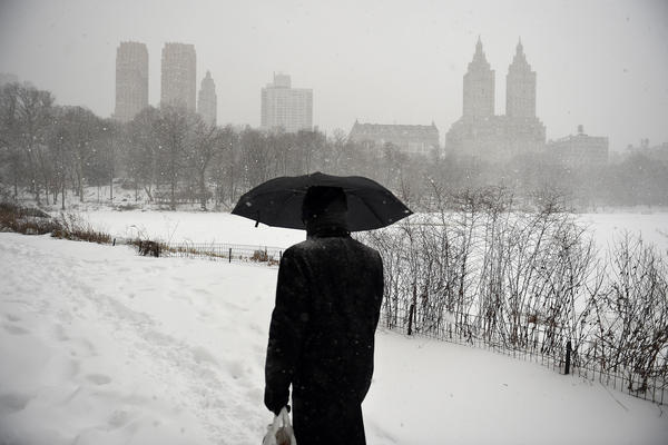 A man walks in heavy snow through Central Park on Saturday in New York City.