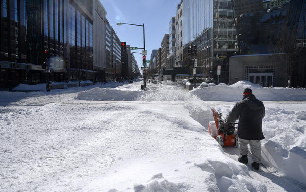 A worker cleans the sidewalk along 19th Street in Washington on Sunday.