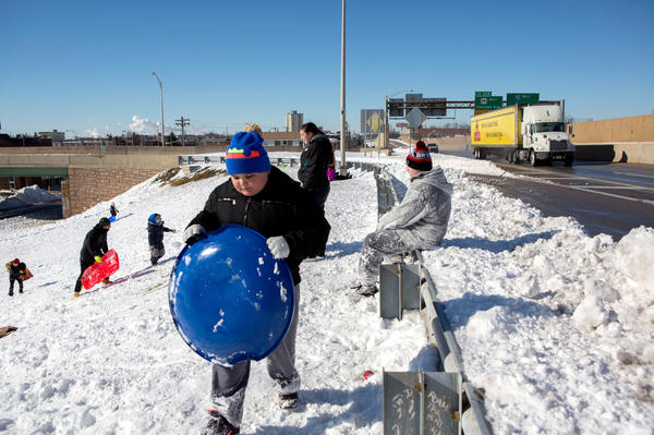 People sled down an on ramp to I-76 West on Sunday in Philadelphia. Millions of people are digging themselves out after a record snowstorm affected most of the Mid-Atlantic states.