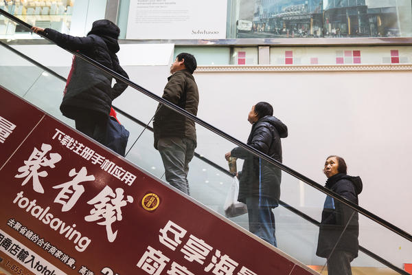 Patrons of the the New World Mall in Flushing ride the escalator from the food court. The Queens neighborhood has become a hot spot for northern Chinese immigrants in the past few years. The trend has brought a cultural wave of influence on the food and business markets in the community.