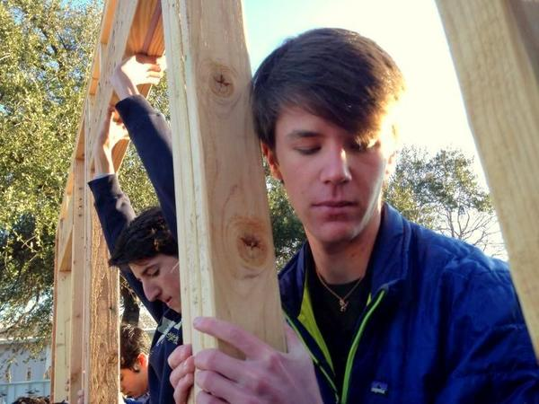 Taylor Thompson (right) helps lift a wall of the Habitat for Humanity house he helped fund.