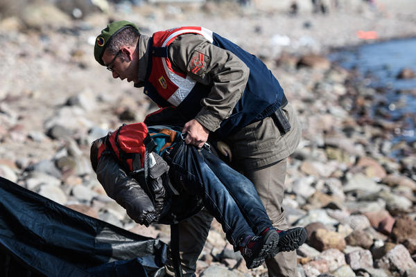 A Turkish gendarme carries the body of a child on a beach in Canakkale, Turkey, on Saturday.