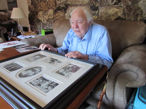 Henry Chamberlain looks at mementos from World War II. He spent three and a half years as a prisoner of the Japanese.