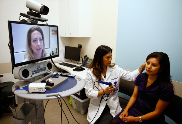 Nurse practitioner Rachelle Quimpo begins an ear exam on Shreya Sasaki at a Kaiser Permanente health clinic inside a Target retail department store in San Diego, Calif., as Dr. Heidi Meyer watches via video. Kaiser says it will train medical students to provide good care beyond traditional medical settings.