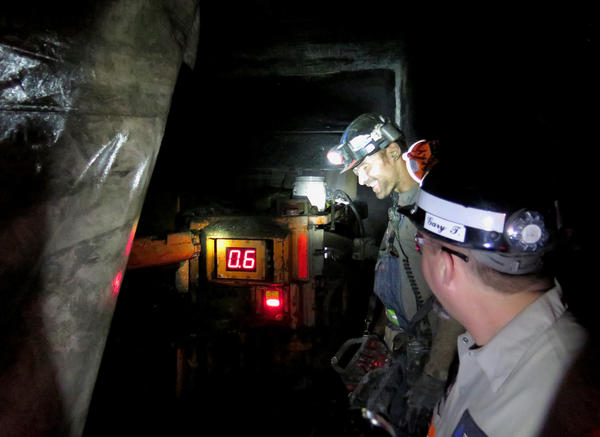 Mine supervisor Gary Thweatt (right) stands with miner Barry McDyer as he operates a continuous miner.